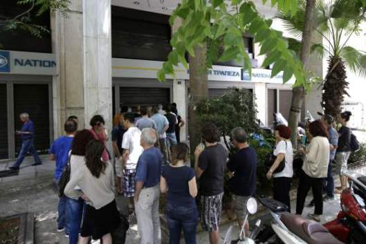 People stand in a queue to use ATMs of a bank in central Athens, Sunday, June 28, 2015. Greece is anxiously awaiting a decision by the European Central Bank on whether to increase the emergency liquidity assistance banks can draw on from the country's central bank. (AP Photo/Thanassis Stavrakis)